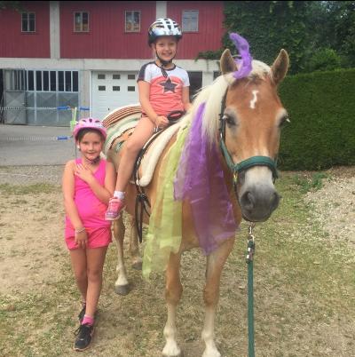 Kinder sitzen auf Pferd